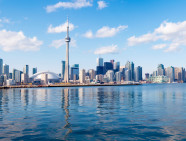 Toronto city skyline, Canada. Downtown area under blue skies and white clouds, reflection in the still waters.