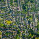 Aerial view over homes, streets and suburban community at the edge of a country town surrounded by green pasture and farmland, Stroud, UK.